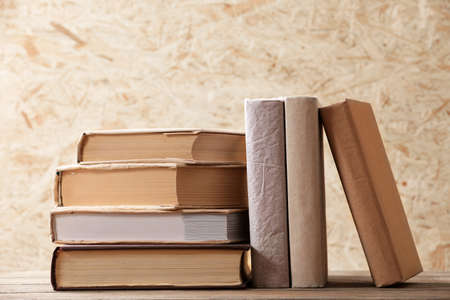 hardboard: Stack of books on wooden hardboard background Stock Photo