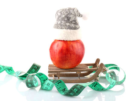 Measuring tape and apple with Christmas decoration isolated on white photo
