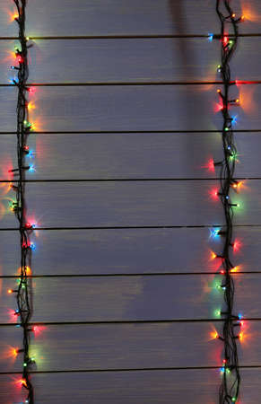 Colorful Christmas lights on wooden planks