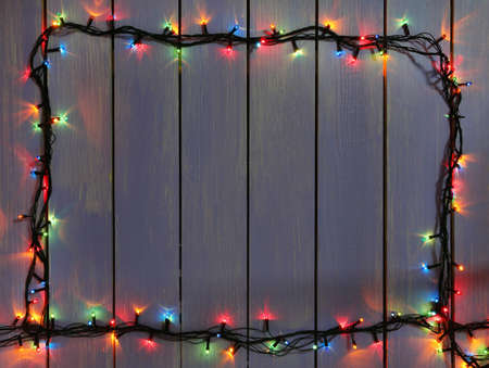 conviviality: Colorful Christmas lights on wooden planks