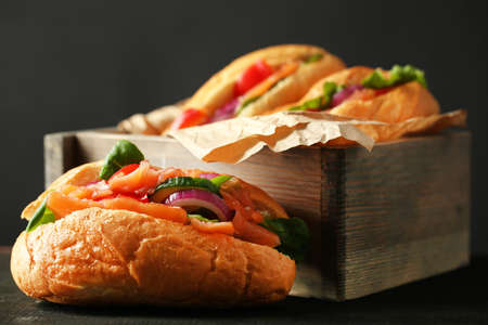 herbs boxes: Sandwiches with salmon in wooden box on dark wooden