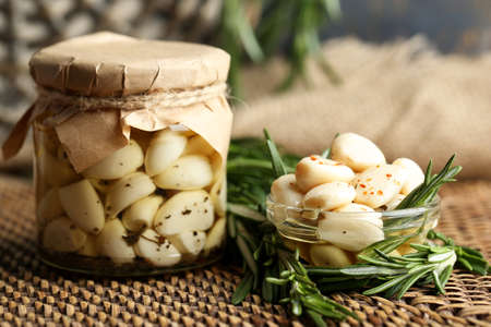 Canned garlic in glass jar and wicker mat and rosemary branches, on wooden  写真素材
