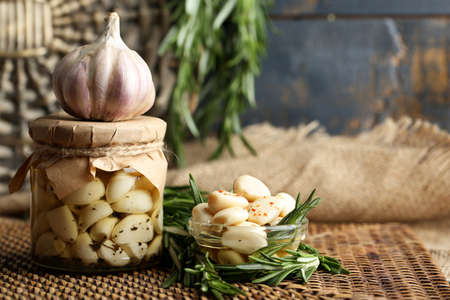 Canned garlic in glass jar and wicker mat and rosemary branches, on wooden  Фото со стока