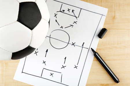 defensive: Scheme football game on sheet of paper and wooden table  Stock Photo