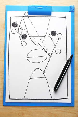 Scheme basketball game on clip board paper with marker and wooden table  photo