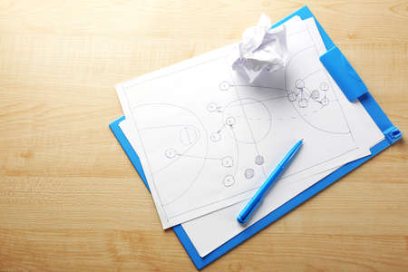 crumpled paper ball: Scheme football game on clip board paper with crumpled ball and pen on wooden table  Stock Photo
