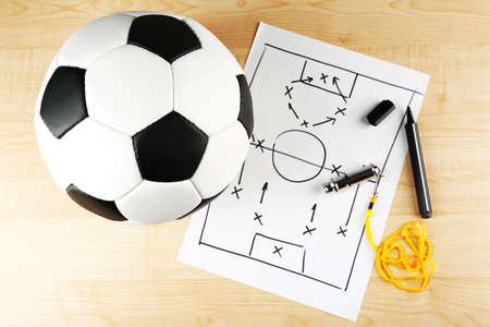 instruction sheet: Scheme football game on sheet of paper and wooden table  Stock Photo