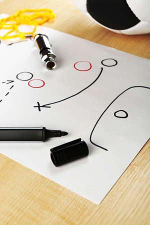 instruction sheet: Scheme football game on sheet of paper and wooden table background