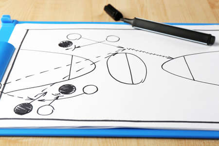 board marker: Scheme basketball game on clip board paper with marker and wooden table background Stock Photo