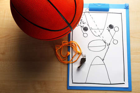 blackboard background: Scheme basketball game on sheet of paper with basketball on wooden table background