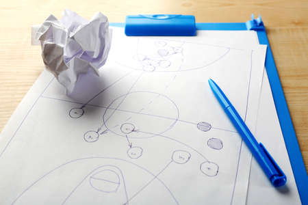 Scheme football game on clip board paper with crumpled ball and pen on wooden table  Stock Photo