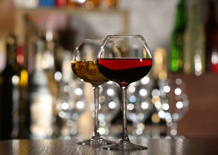white wine glass: Two glasses of wine with bar on background Stock Photo