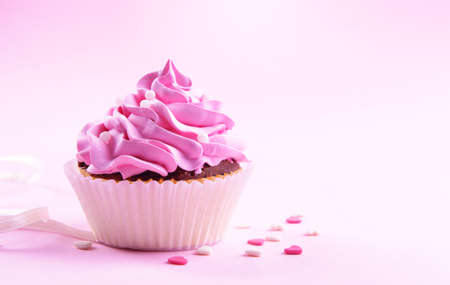 Delicious cupcake on pink background photo