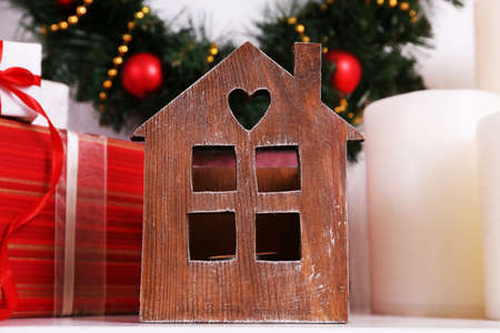 mantelpiece: Christmas decoration with wreath, candles and present boxes on shelf on white wall background