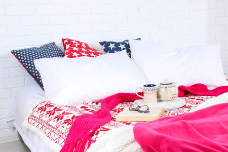 bedsheets: Book and tea on bed close-up