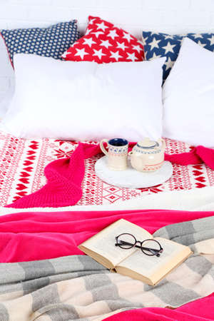 bedsheets: Libro e t� sul letto close-up Archivio Fotografico