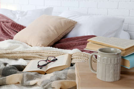 本とベッドのクローズ アップのメガネ