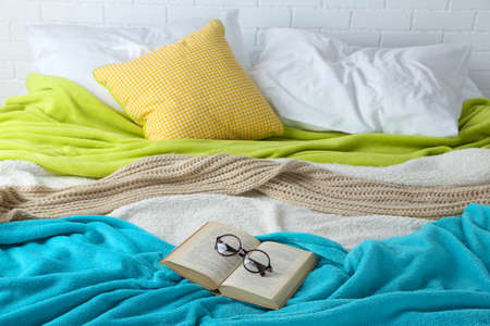 bedsheets: Book and glasses on bed close-up
