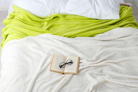 Boek en glazen op bedclose-up Stockfoto