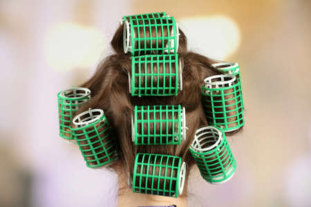 Long female hair during hair dressing with curler, close-up photo