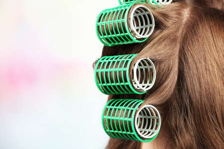 curler: Long female hair during hair dressing with curler, close-up, on light background