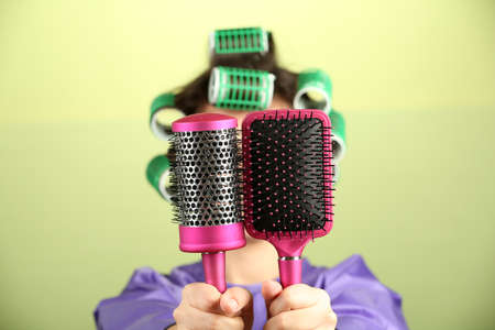 hair curlers: Girl in hair curlers  holding hair combs on colorful background