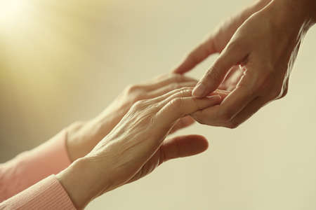 working with hands: Old and young holding hands on light background, closeup