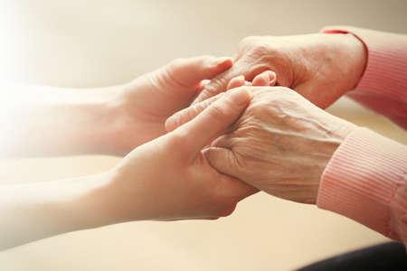 mãos: Velhas e novas Mãos Dadas no fundo claro, close up