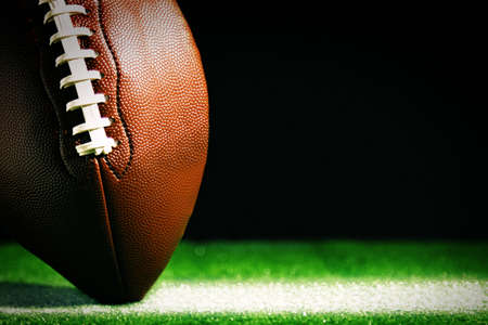 footballs: American football on green grass, on black background