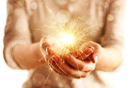Hände mit Wunderkerze Licht isoliert auf weiß