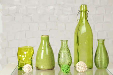 ceramic bottle: Interior with decorative vases on table top and white brick wall background