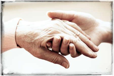 Oude en jonge handen houden op lichte achtergrond, close-up Stockfoto