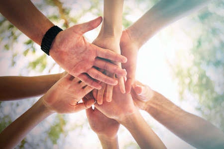 teamwork  together: Hands of young people close up on sunny nature background Stock Photo