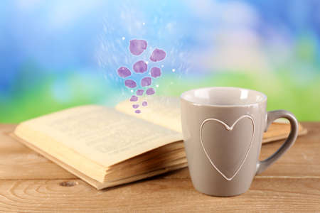 Open book with flying petals on table on bright background photo