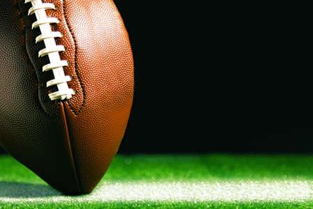 American football op groen gras, op een zwarte achtergrond Stockfoto