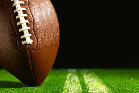american football: American football on green grass on black background
