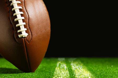 American football op groen gras op een zwarte achtergrond Stockfoto