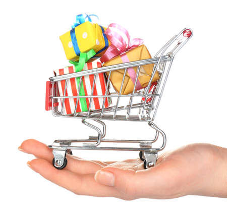 christmas budget: Female hand with small shopping cart full of gifts, isolated on white Stock Photo