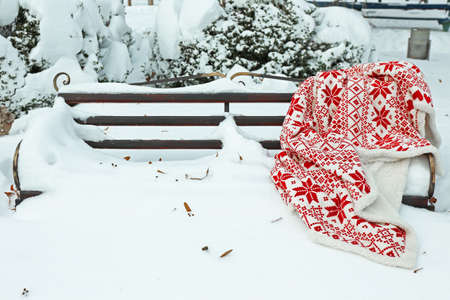 Warm plaid on bench in park in winter time photo