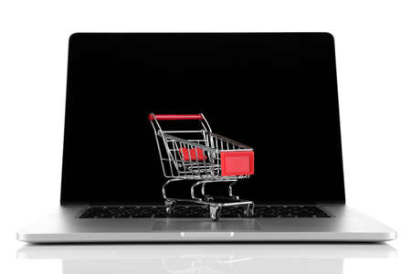 Laptop with small shopping cart isolated on white background photo