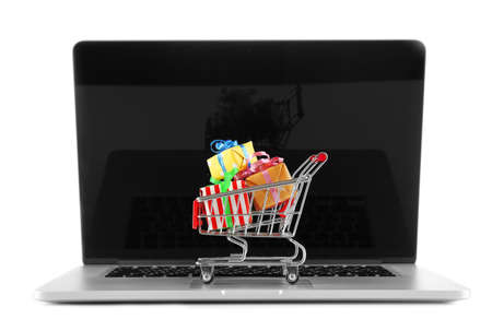 christmas budget: Laptop with small shopping cart full of gifts isolated on white background Stock Photo