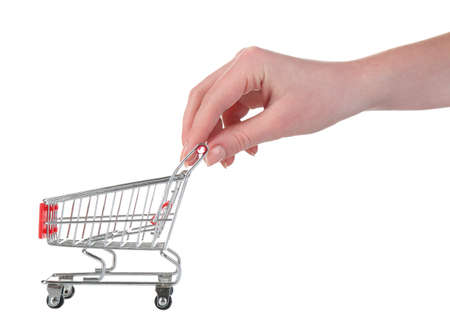 Small shopping cart in female hand isolated on white photo