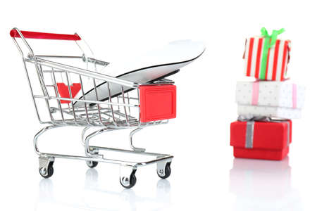 christmas budget: Small shopping cart with computer mouse and present boxes isolated on white
