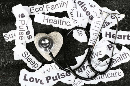 Decorative heart  with stethoscope on background of paper notes photo