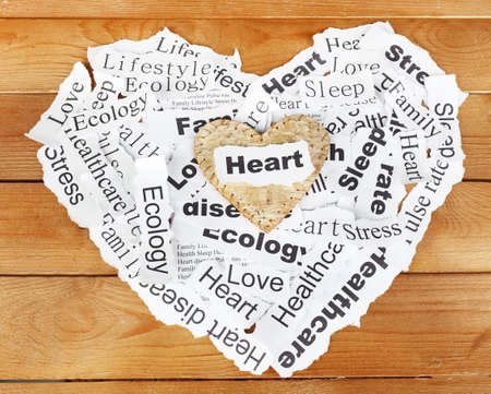 Decorative heart on paper notes, on wooden background photo