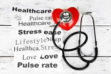 Decorative heart with stethoscope on paper notes, on wooden background photo