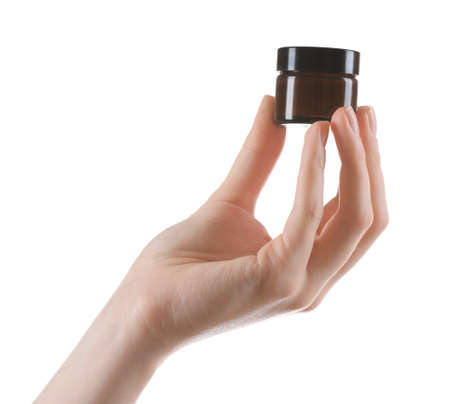 Female hand with cosmetics bottle isolated on white photo