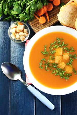Composition with carrot soup, ingredients and herbs on color wooden background photo