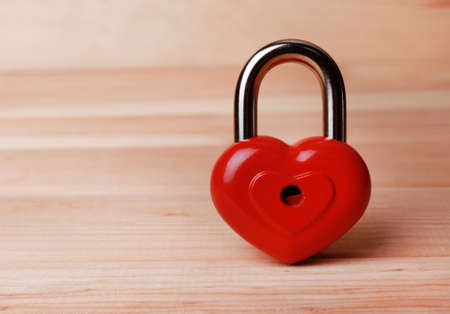 Heart-shaped padlock on wooden background photo