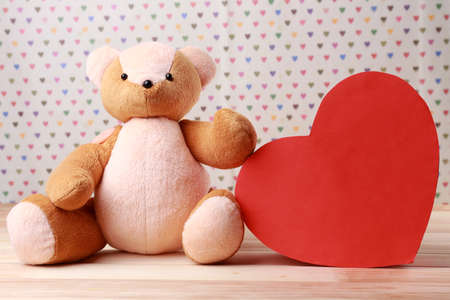 shame: Teddy Bear with red heart on festive background Stock Photo